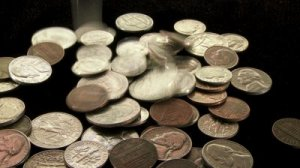 stock-footage-american-coins-dropping-into-frame-with-black-background